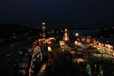 View from the top of the Ferris wheel. Out in the distance, past the flash and glitter of the midway, lie the lights of the refineries that built southwest Tulsa; at left, cars approach on historic Route 66.