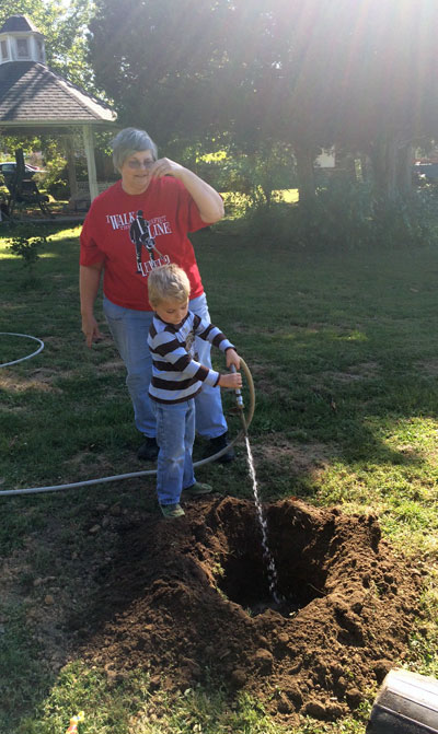 Grandma helped Ollie fill the hole with water before planting his tree.
